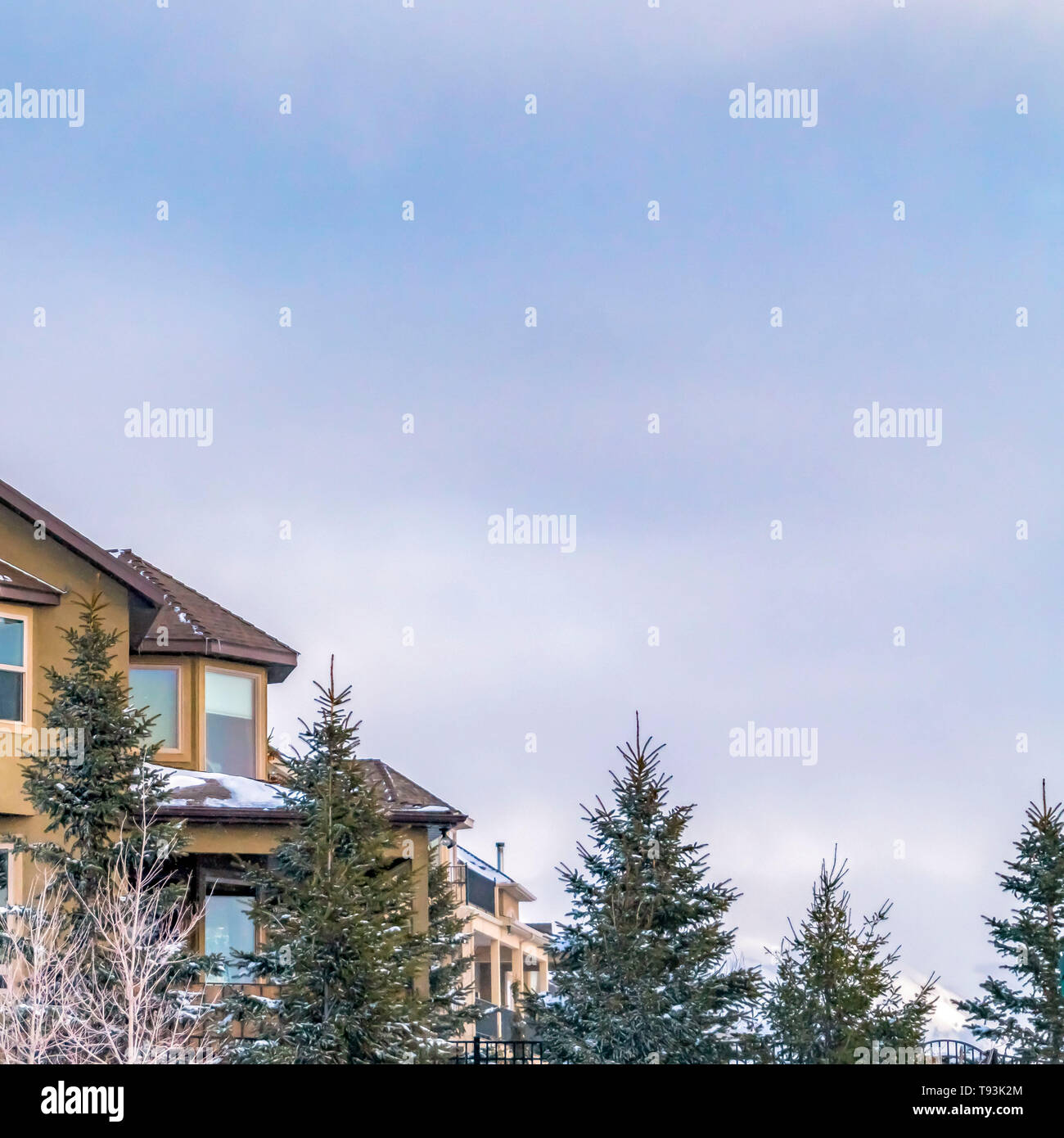 Square Exterior of an elegant house against blue sky with puffy clouds in winter - Stock Image