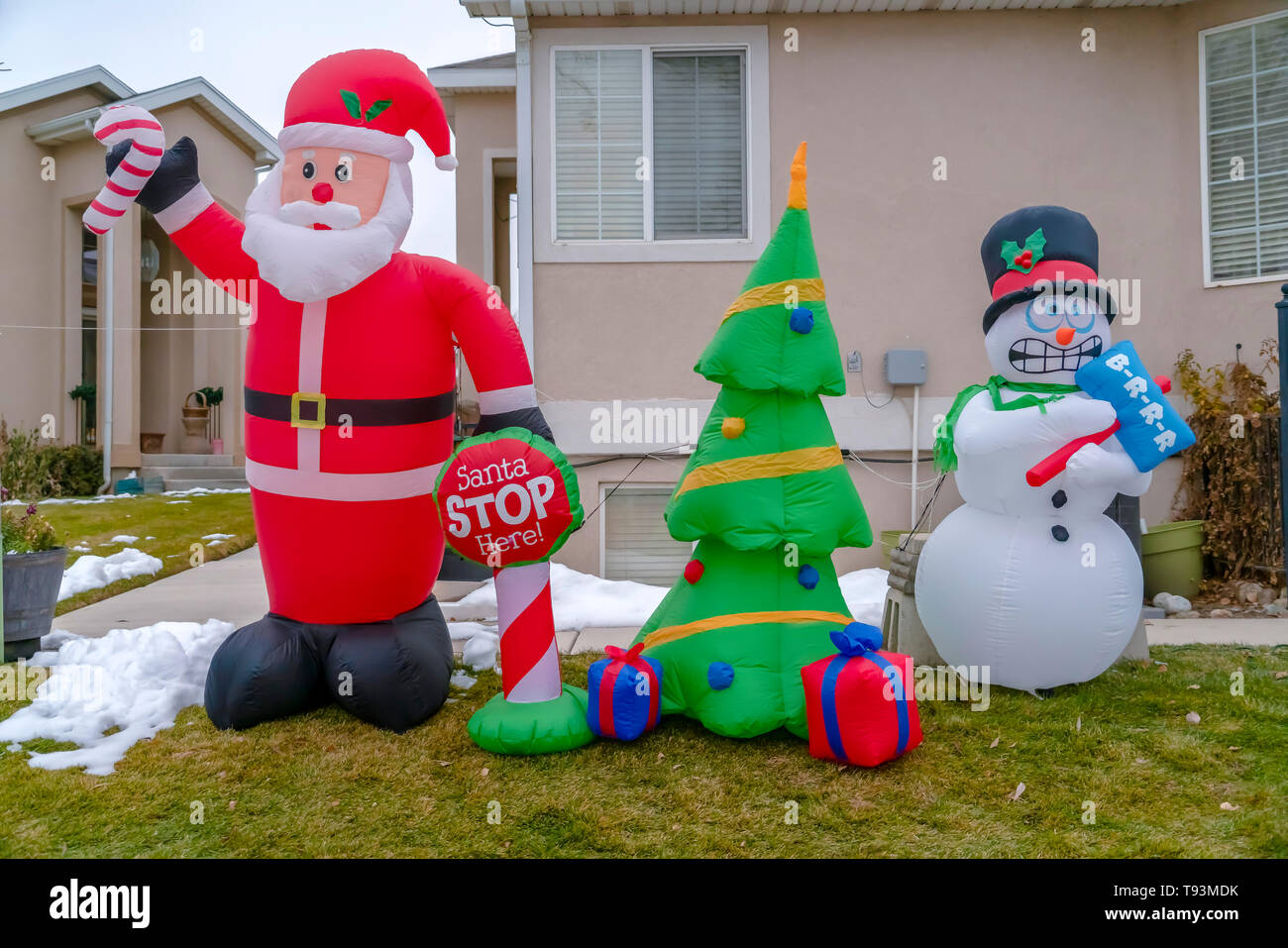 Inflatable Christmas Decorations On A Grassy Yard With Snow In