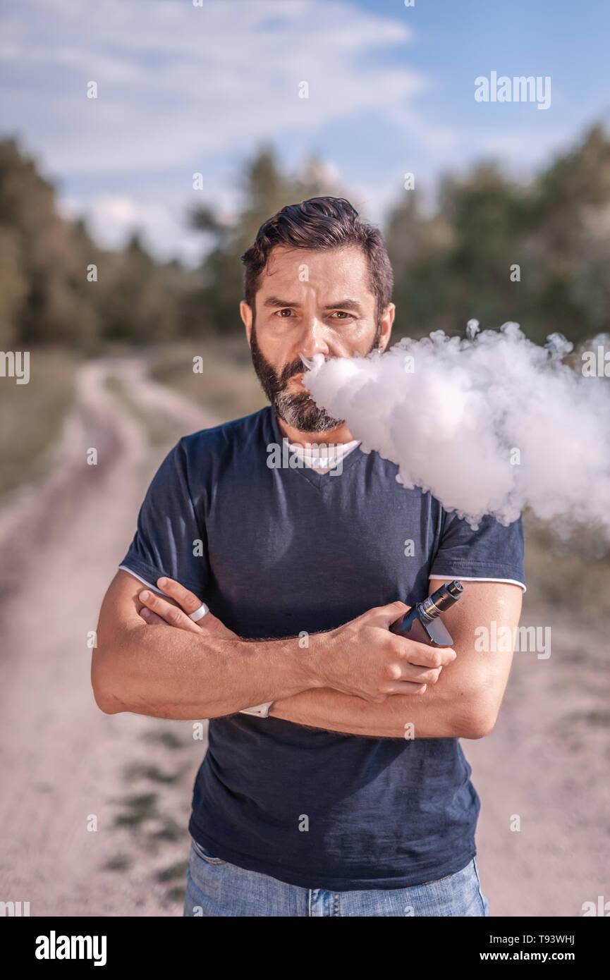 Confident vaper enjoying electronic cigarette outside. Man really likes process of smoking. - Stock Image