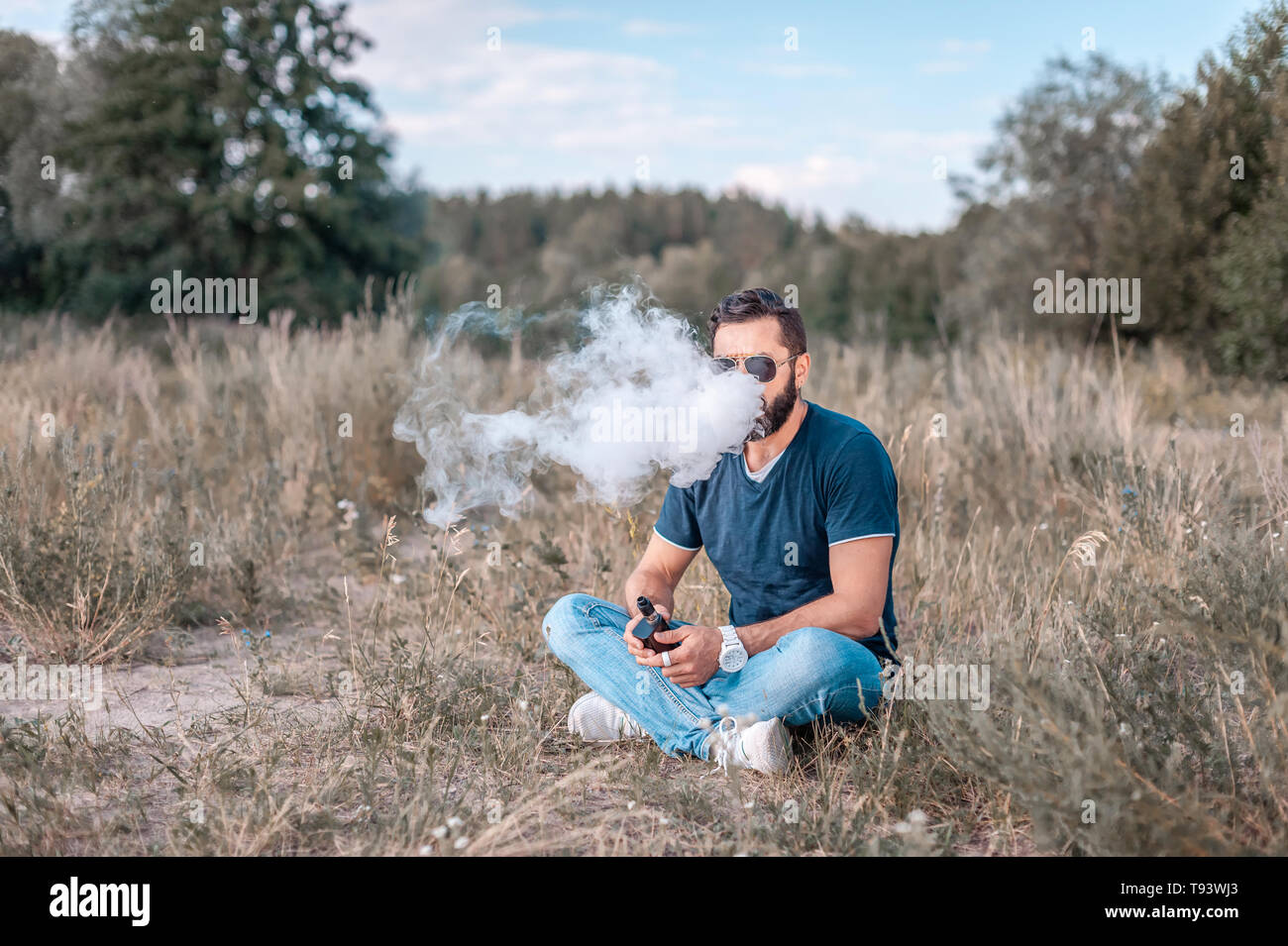 Brutal man smoke electronic cigarette and exhals smoke cloud. Vaping concept. - Stock Image