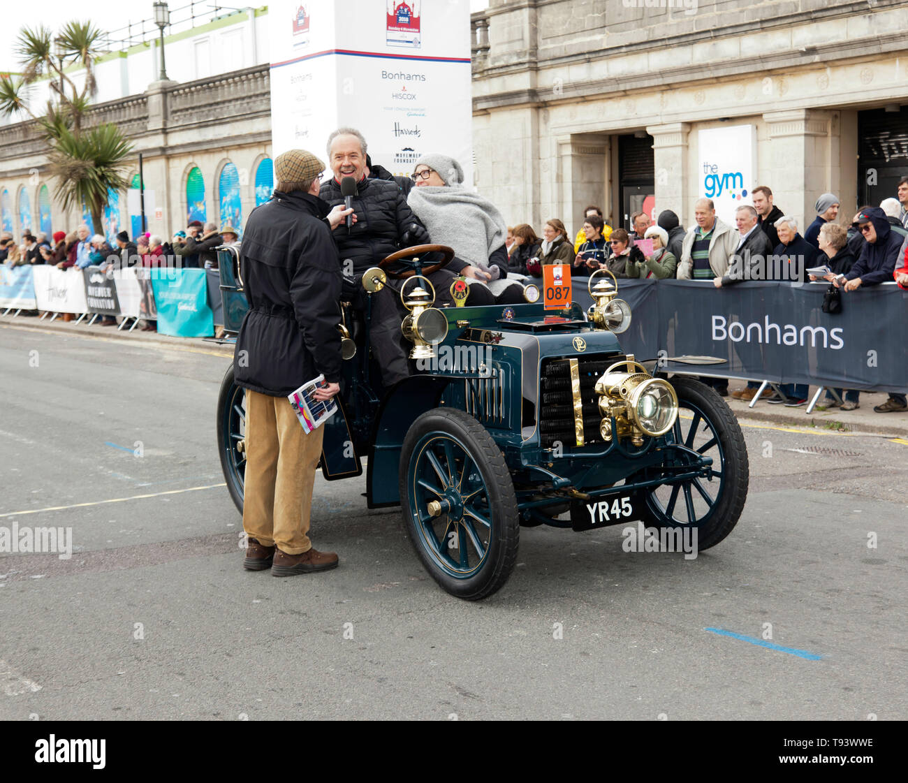 Mr Ian Gwynne being interviewed, after successfully completing the 2018 London to Brighton Veteran Car Run, in a 1901 Panhard Et Levassor. Stock Photo
