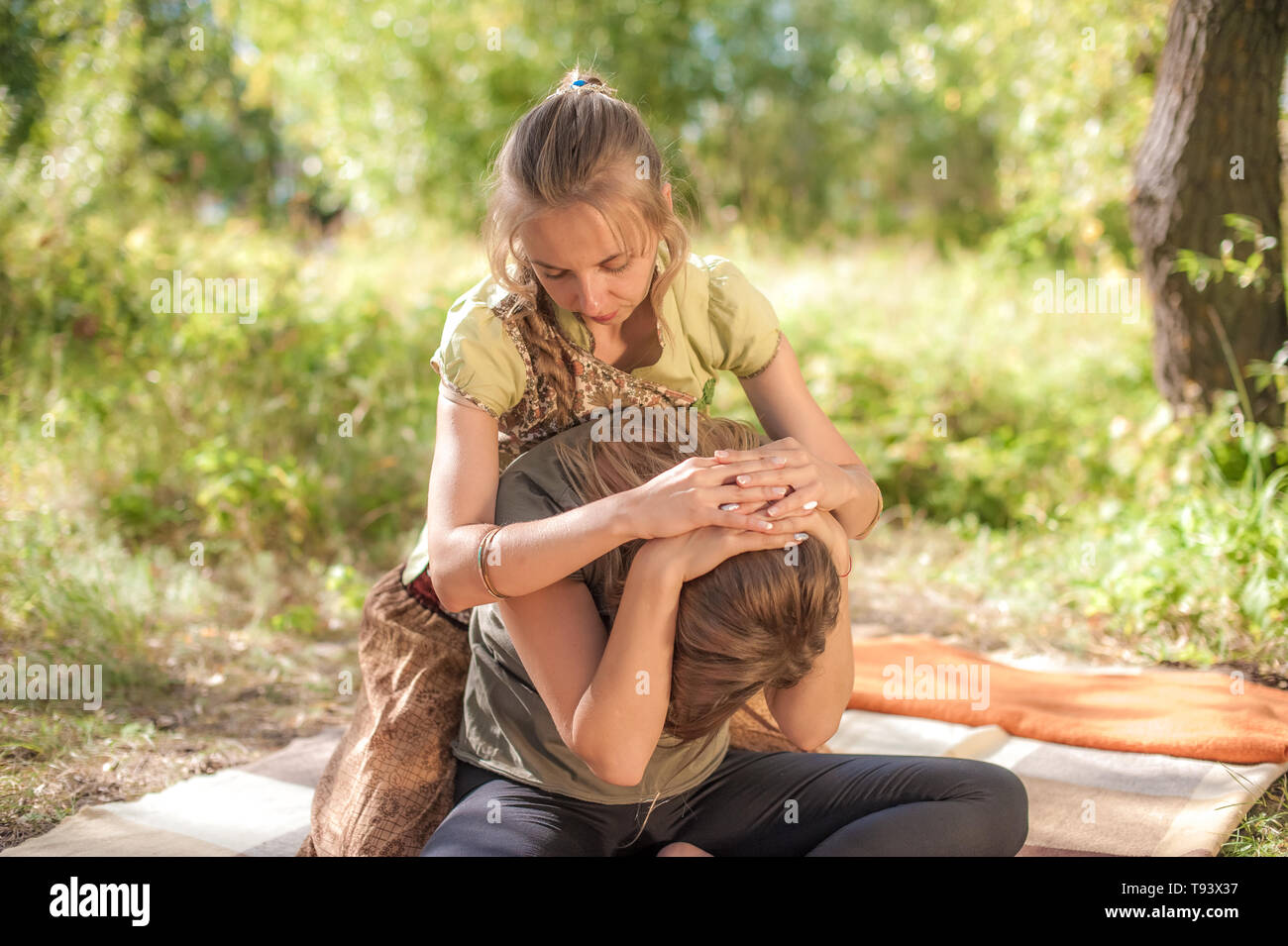 Experienced masseuse thuroughly massages a girl on the grass. - Stock Image