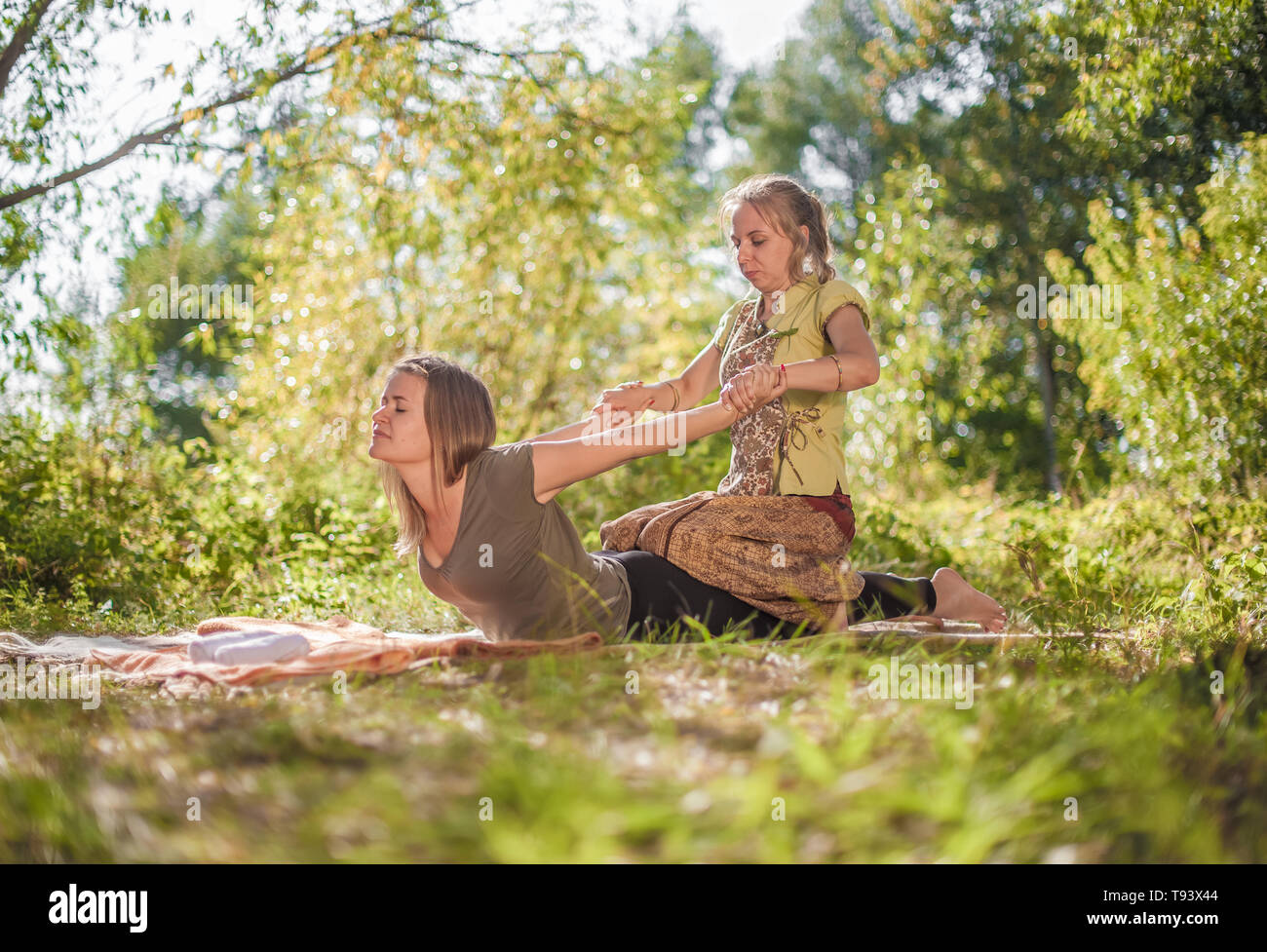 Girl masseuse thuroughly massages a girl outside. - Stock Image