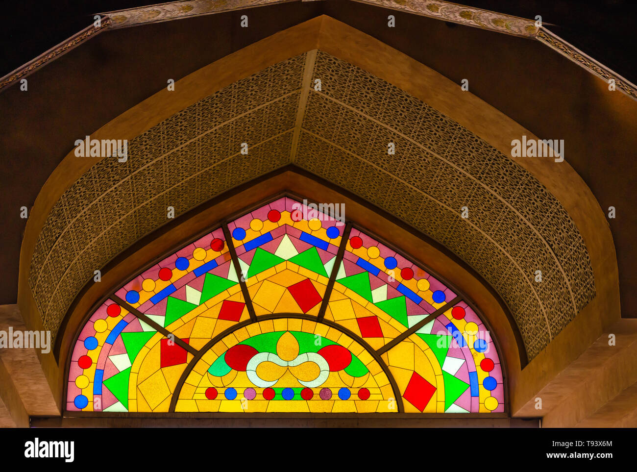 Traditional Middle Eastern style stained glass art on a huge arch. From Muscat, Oman. - Stock Image