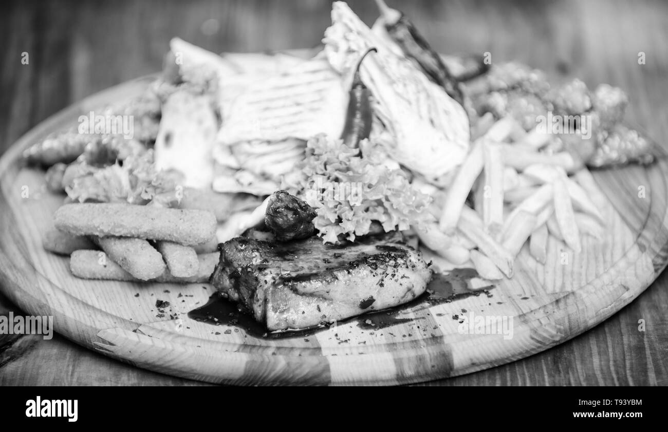 Snack for beer. Wooden board french fries fish sticks burrito and meat steak served with salad. Pub menu snack. Enjoy your meal. Meat snack for group friends. Tasty delicious snacks. Restaurant food. - Stock Image