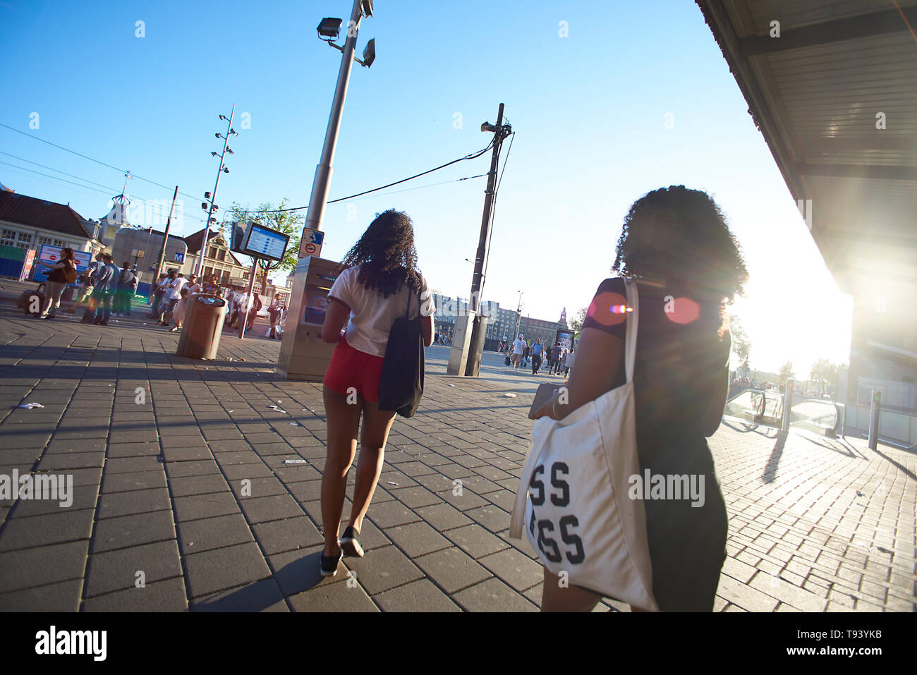 Two African women arriving at Amsterdam central statiion and walking down the square towards the city centre in spring sunhine - Stock Image