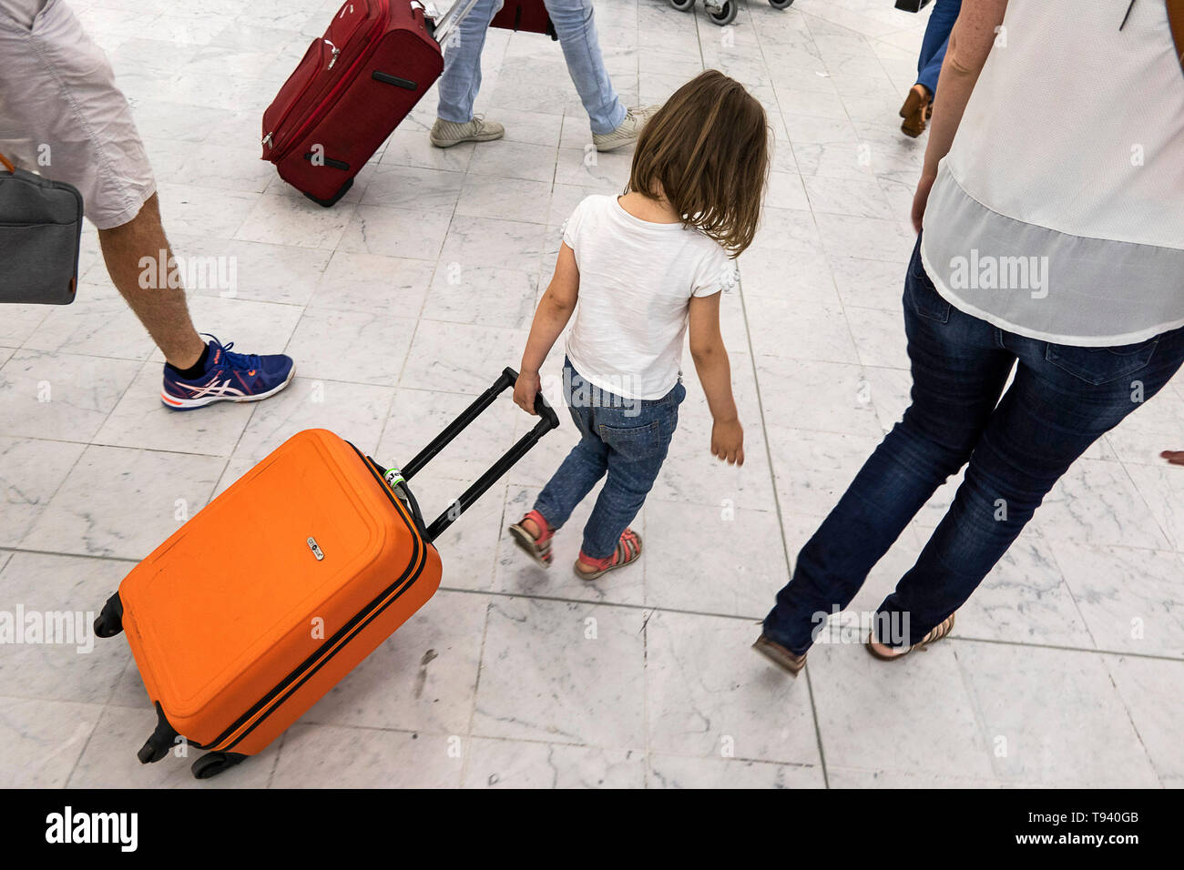 Little girl with head down pulling an orange trolley case in a hall of Orly Airport - Stock Image
