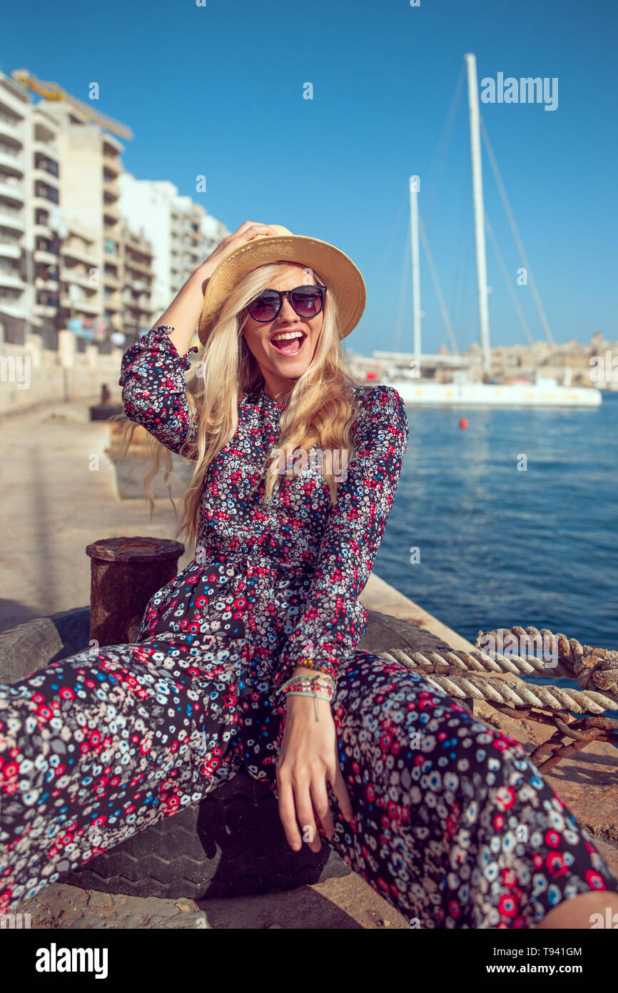 Happy fashionable mediterranean woman in hat laughing at harbour dock Stock Photo