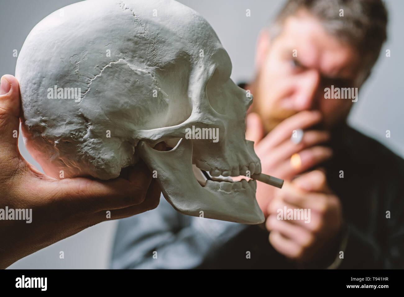 Man smoking cigarette near human skull symbol of death. Harmful habits. Smoking cause health damage and death. Destroy your health. Smoking is harmful. Habit to smoke tobacco bring harm to your body. - Stock Image