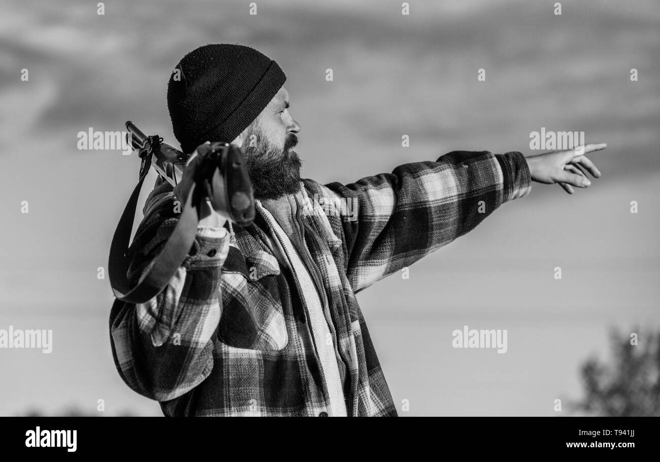 Man brutal unshaved gamekeeper nature background. Hunting permit. Hunting brutal masculine hobby. Hunting and trapping seasons. Bearded serious hunter spend leisure hunting. Look there. Noticed game. - Stock Image