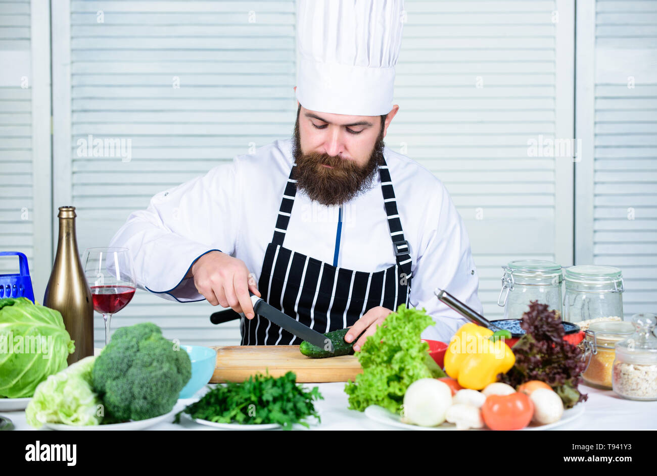 According to recipe. Prepare ingredient for cooking. Useful for significant amount of cooking methods. Basic cooking processes. Man master chef or amateur cooking food. Sharp knife chopping vegetable. - Stock Image