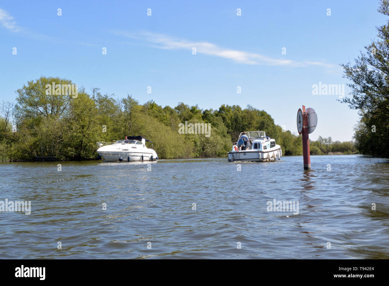 Cabin cruisers pass each other on the River Ant at the southern end of Barton Broad, Broads National Park, Norfolk, UK Stock Photo