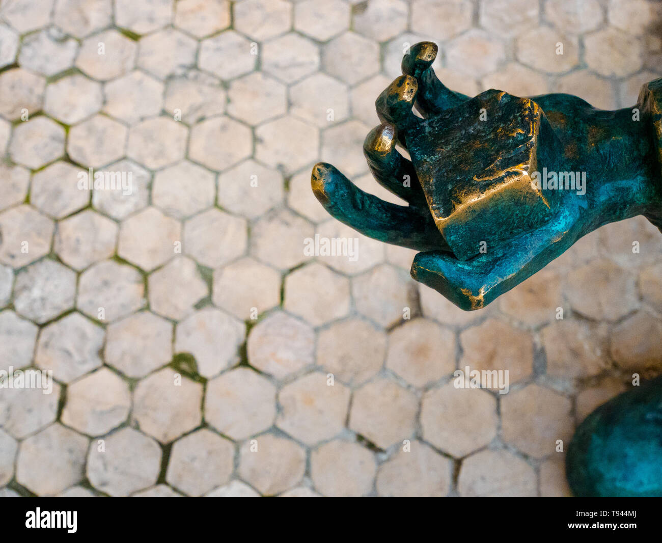 detail of bronze statue, a hand holding a paved stone Lisbon, Portugal - Stock Image