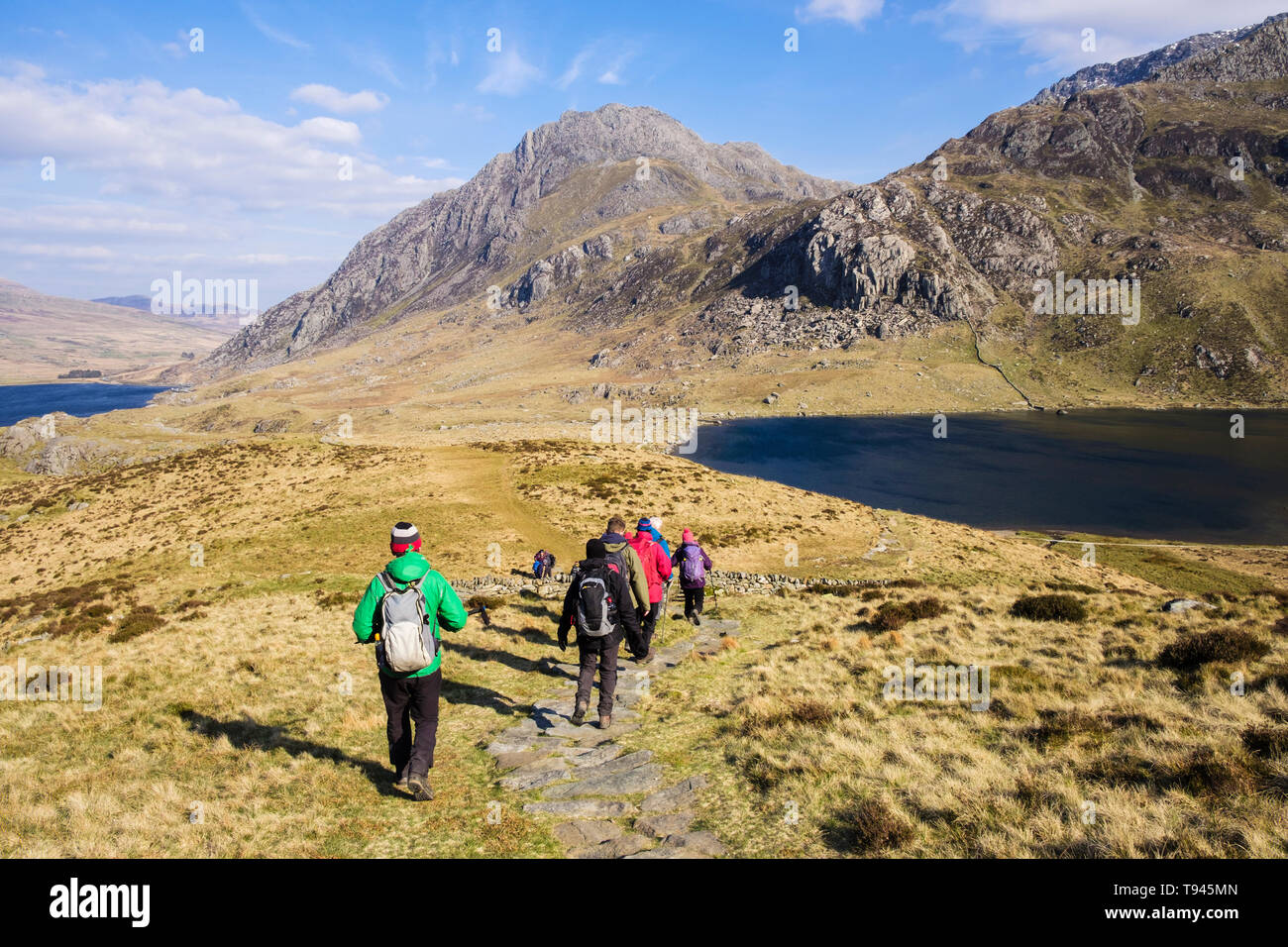 Hikers hiking down Y Garn mountain path to Llyn Idwal lake in Cwm Idwal in mountains of Snowdonia National Park. Ogwen, Gwynedd, Wales, UK, Britain - Stock Image