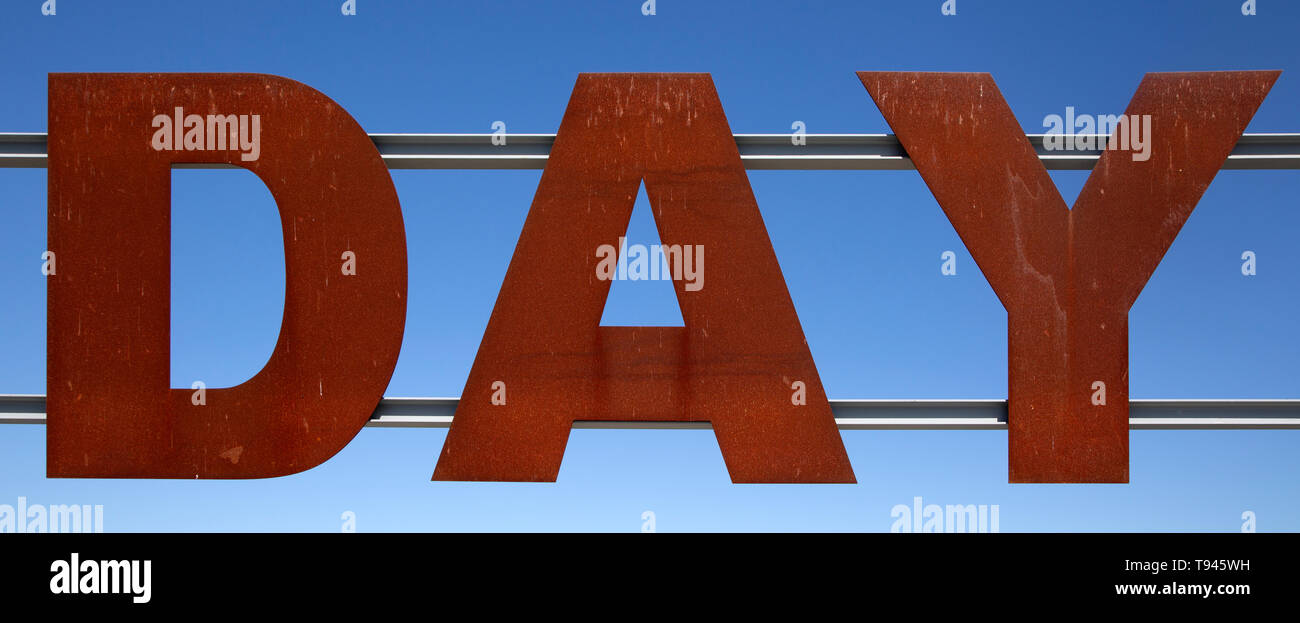 Large red rusty capital letters spell the word DAY against blue sky background, Alqueva dam, Moura, Portugal - Stock Image