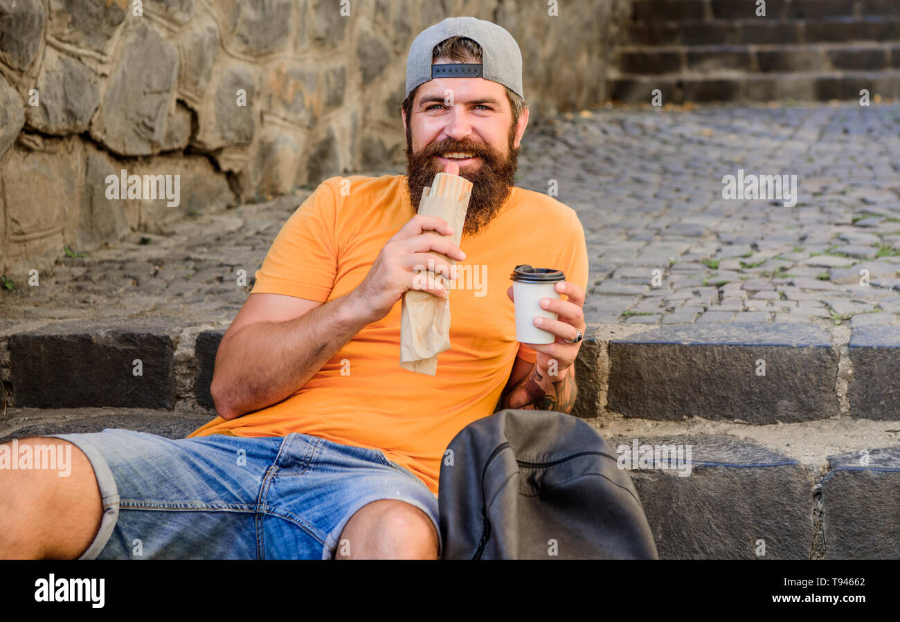 Junk food. Guy eating hot dog. Man bearded enjoy quick snack and drink paper cup. Street food so good. Urban lifestyle nutrition. Carefree hipster eat junk food while sit on stairs. Hungry man snack. - Stock Image