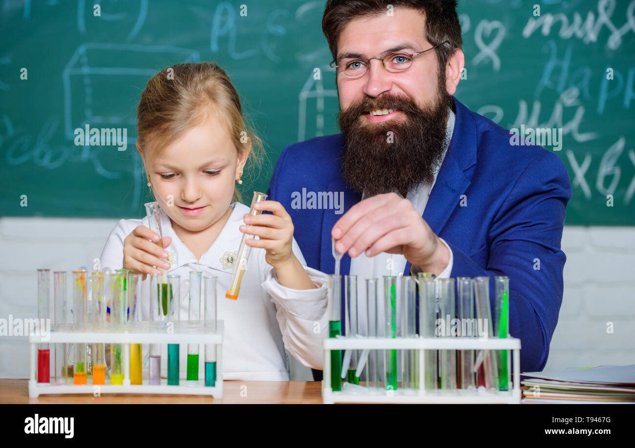 Explaining chemistry to kid. How to interest children study. Fascinating chemistry lesson. Man bearded teacher and pupil with test tubes in classroom. Private lesson. School chemistry experiment. - Stock Image
