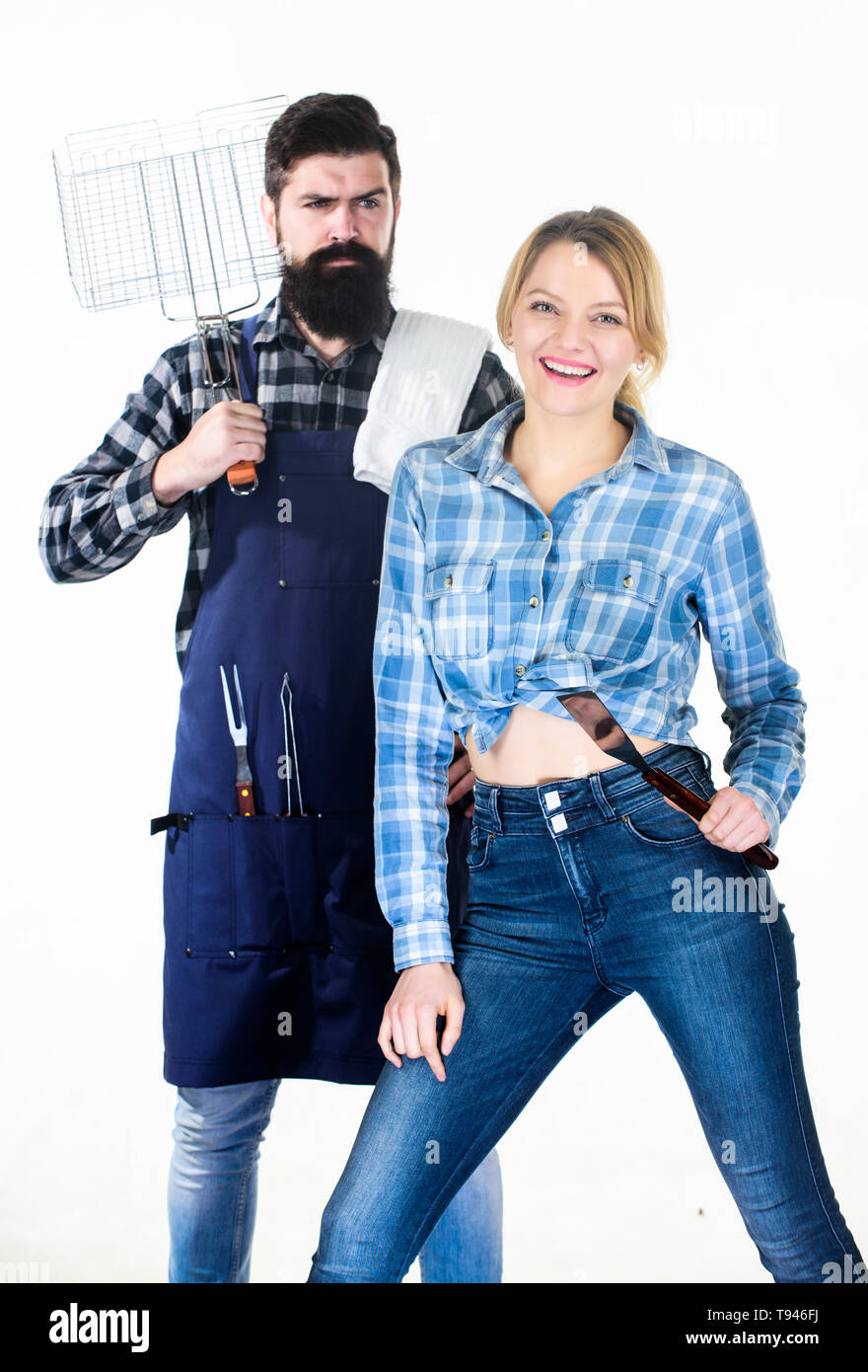 Family weekend. Sharing good time. Picnic barbecue. food cooking recipe. Tools for roasting meat. Couple in love hold kitchen utensils. Man bearded hipster and girl. Preparation and culinary. - Stock Image
