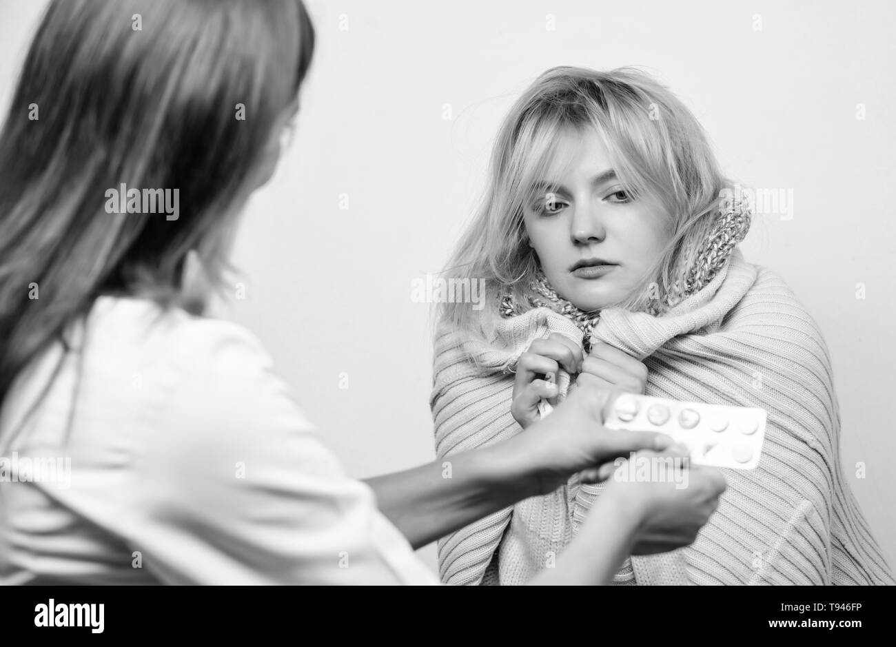 Getting medical help. Primary care doctor making diagnosis to sick woman. Doctor visiting unhealthy woman at home. Medical doctor examining patient. Patient care and healthcare. - Stock Image