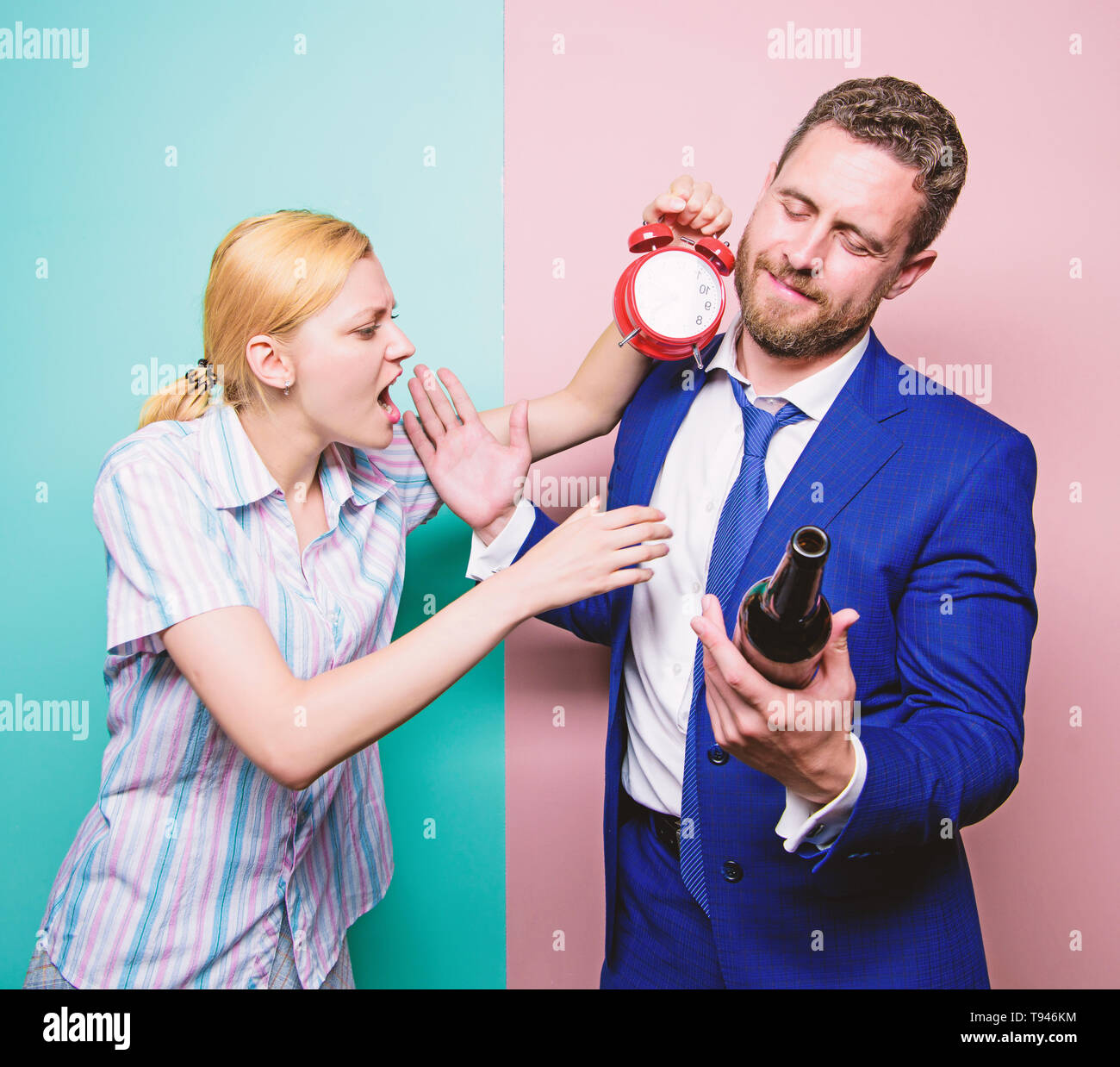 Caught for coming home late. Man suffering from alcoholism. Angry wife meeting drunk husband late at home. Businessman with alcohol bottle and woman with clock. Addictive alcoholism or alcohol abuse. - Stock Image