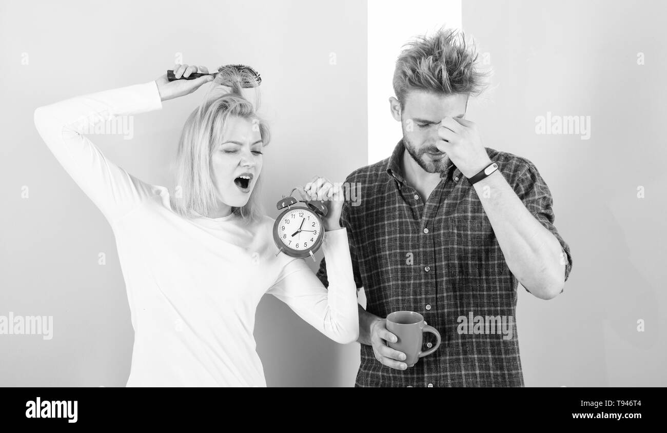 Regret late regime. Couple morning awakening alarm clock. Create healthy rest regime to sleep enough. We should go to bed earlier. Woman and man sleepy tousled hair drink morning coffee. - Stock Image