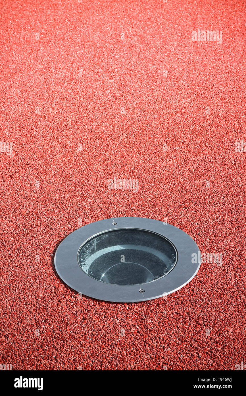 Recessed floor lamp on red gravel floor - image with copy space - Stock Image