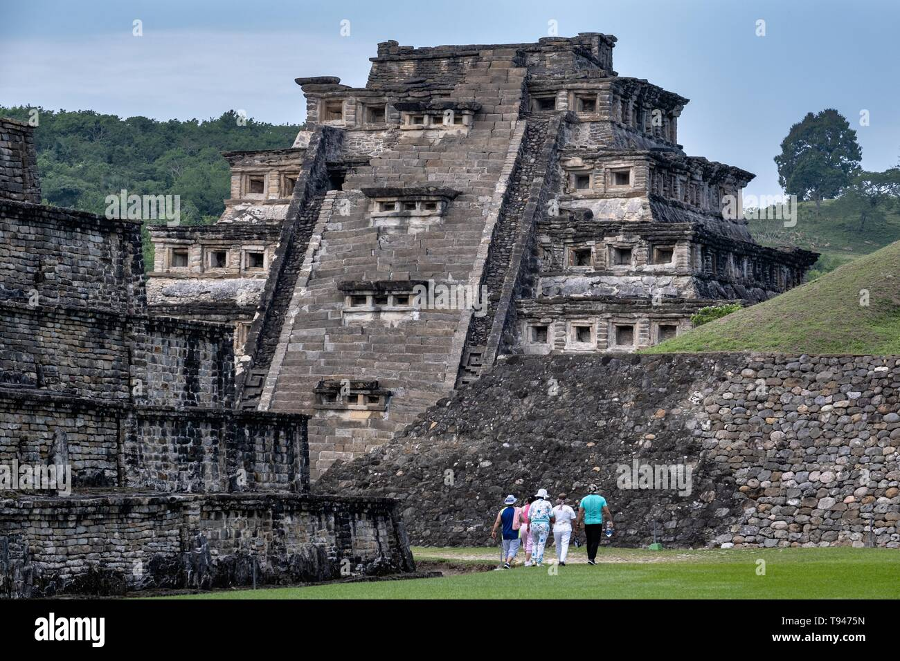 Tourists walk toward the Mesoamerica Pyramid of the Niches at the pre-Columbian archeological complex of El Tajin in Tajin, Veracruz, Mexico. El Tajín flourished from 600 to 1200 CE and during this time numerous temples, palaces, ballcourts, and pyramids were built by the Totonac people and is one of the largest and most important cities of the Classic era of Mesoamerica. - Stock Image