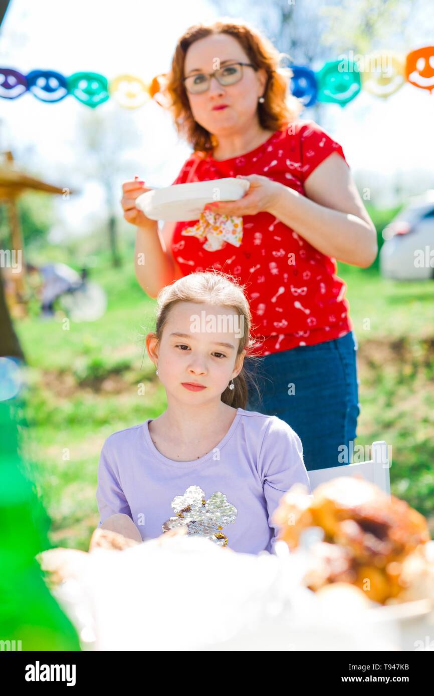 Sad teen aged girl gloomily sitting by table on birthday garden party, mother behind eating - sunny day - Stock Image