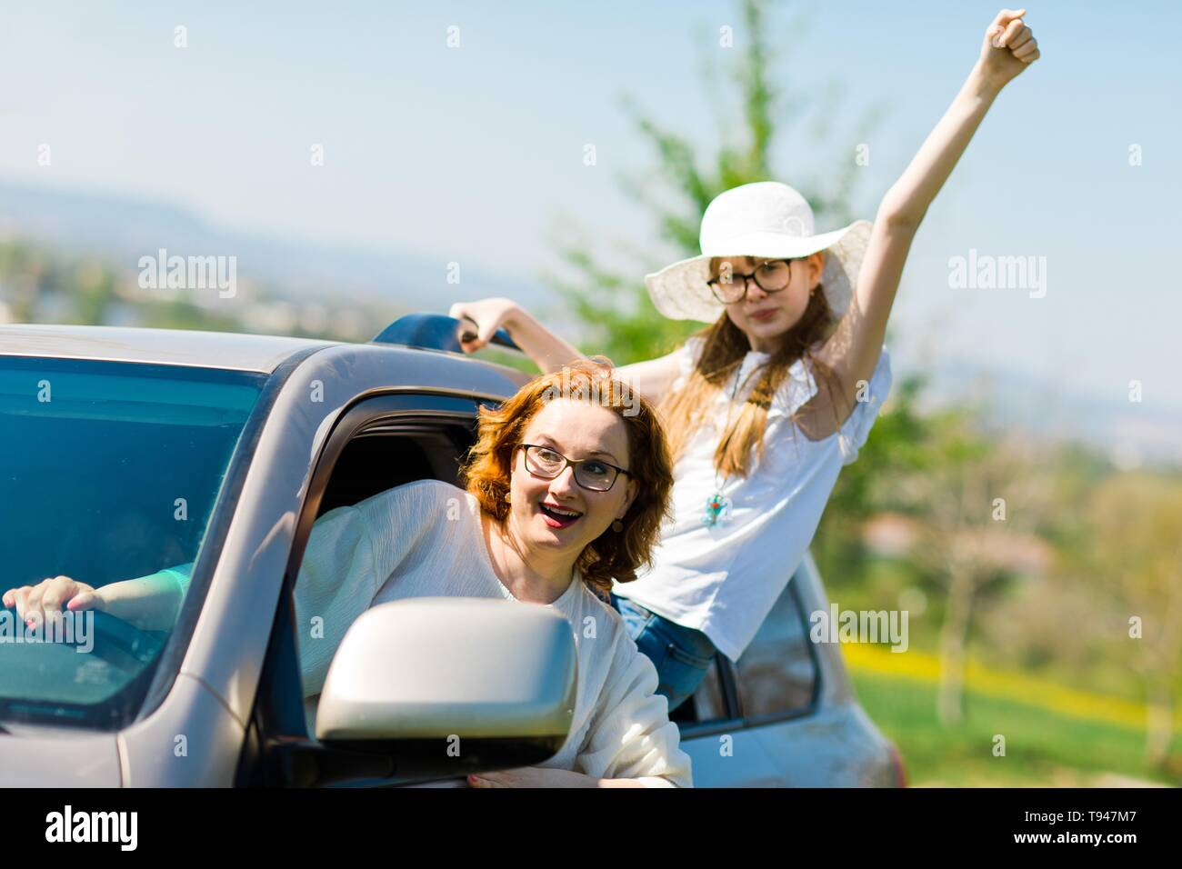 Rioters behind the wheel, female hooligans in the car showing gestures around Stock Photo