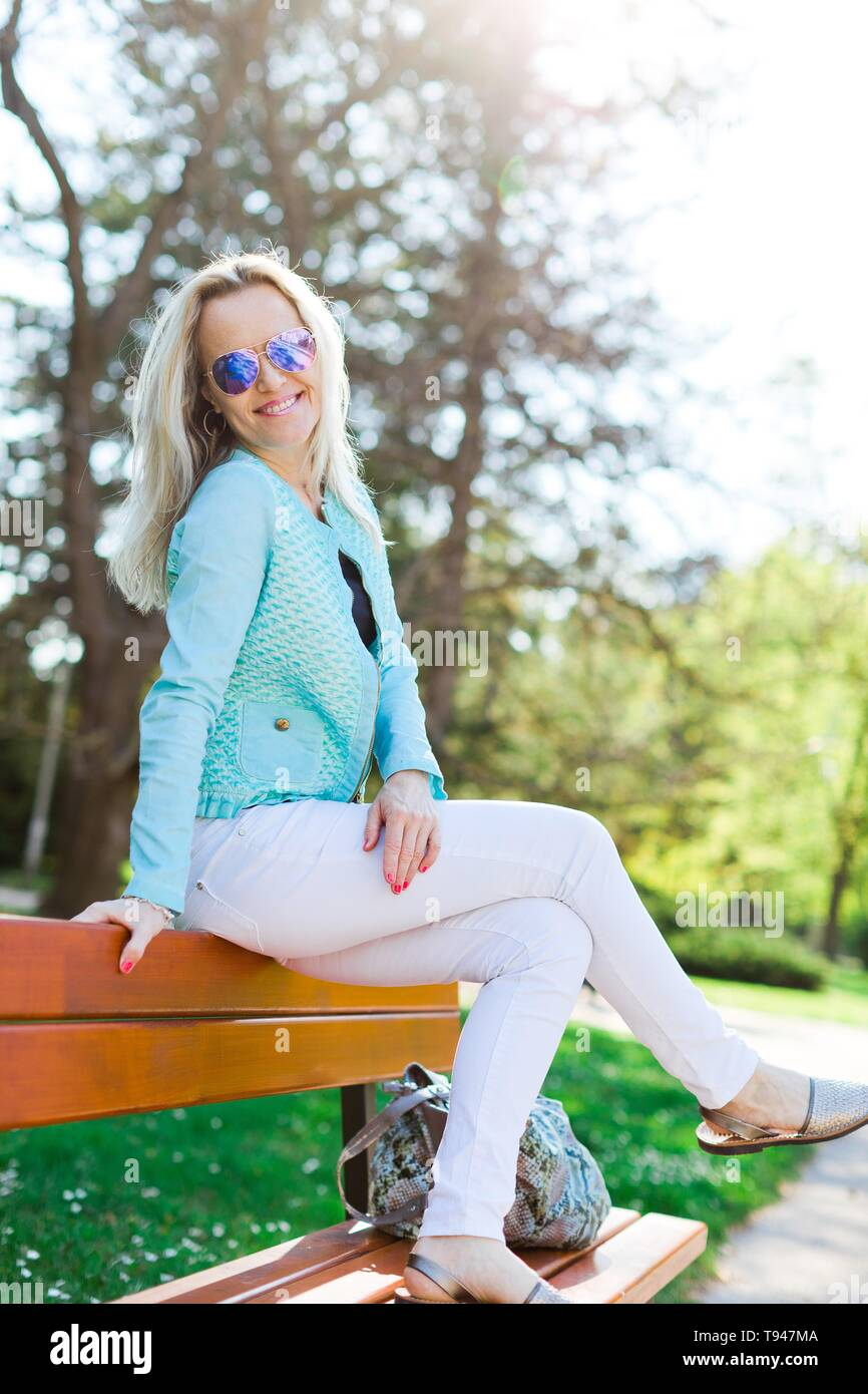Blond attractive woman with sun glasses siting on bench - summer sunny day - Stock Image
