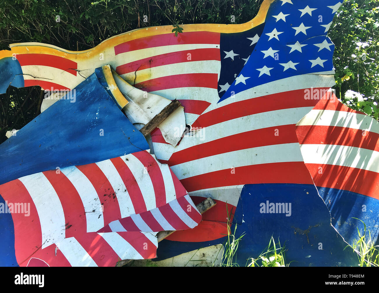 Broken flag, demolished background cardboard with American flag 'Stars and Stripes' as motive, disposed at the roadside. - Stock Image