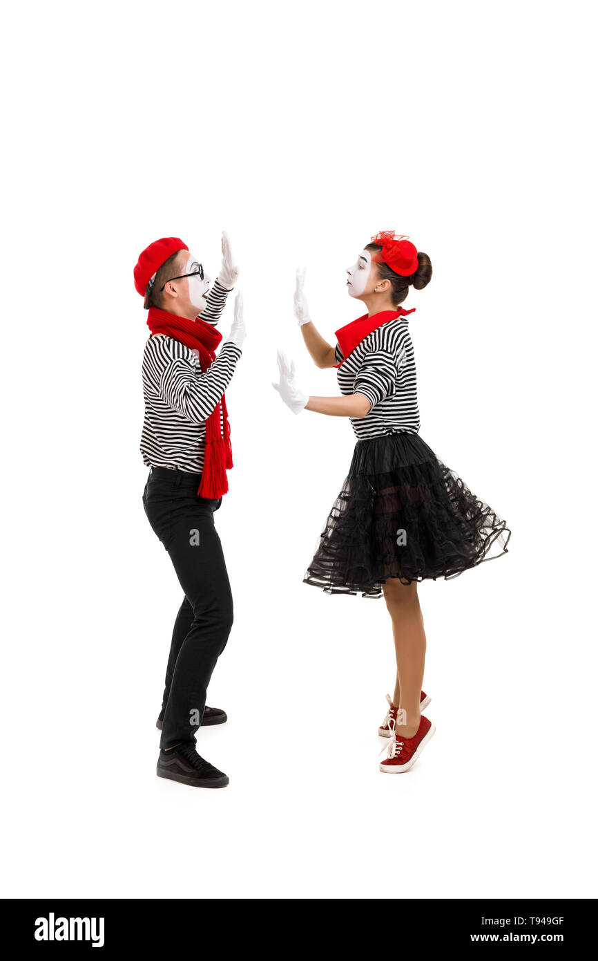 mimes in striped shirts. Male and female mimes dancing isolated on white background - Stock Image