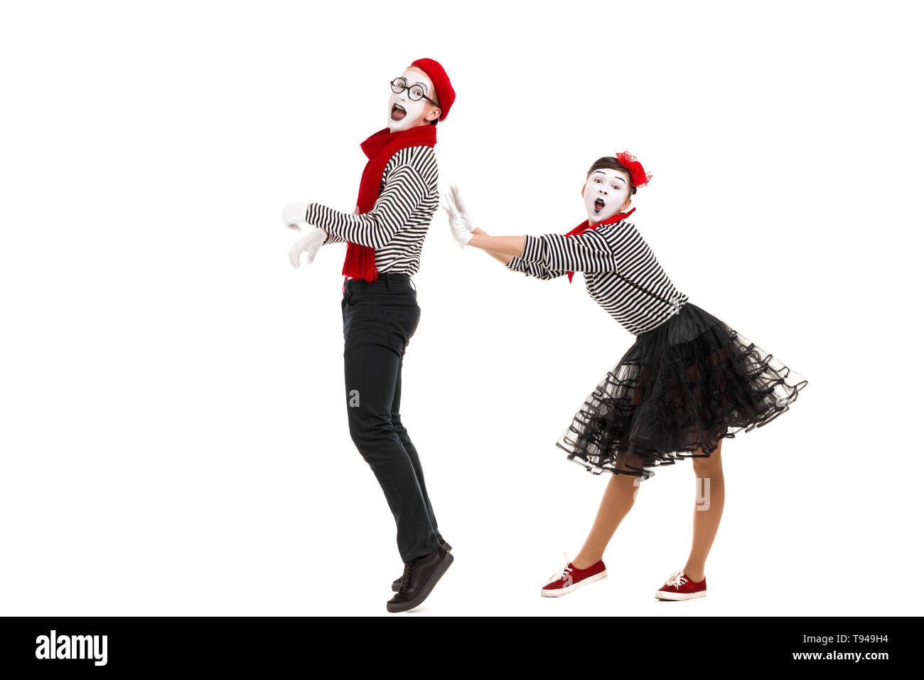 surprised mimes in striped shirts. Man and woman dressed as actors of pantomime theater isolated on white background - Stock Image