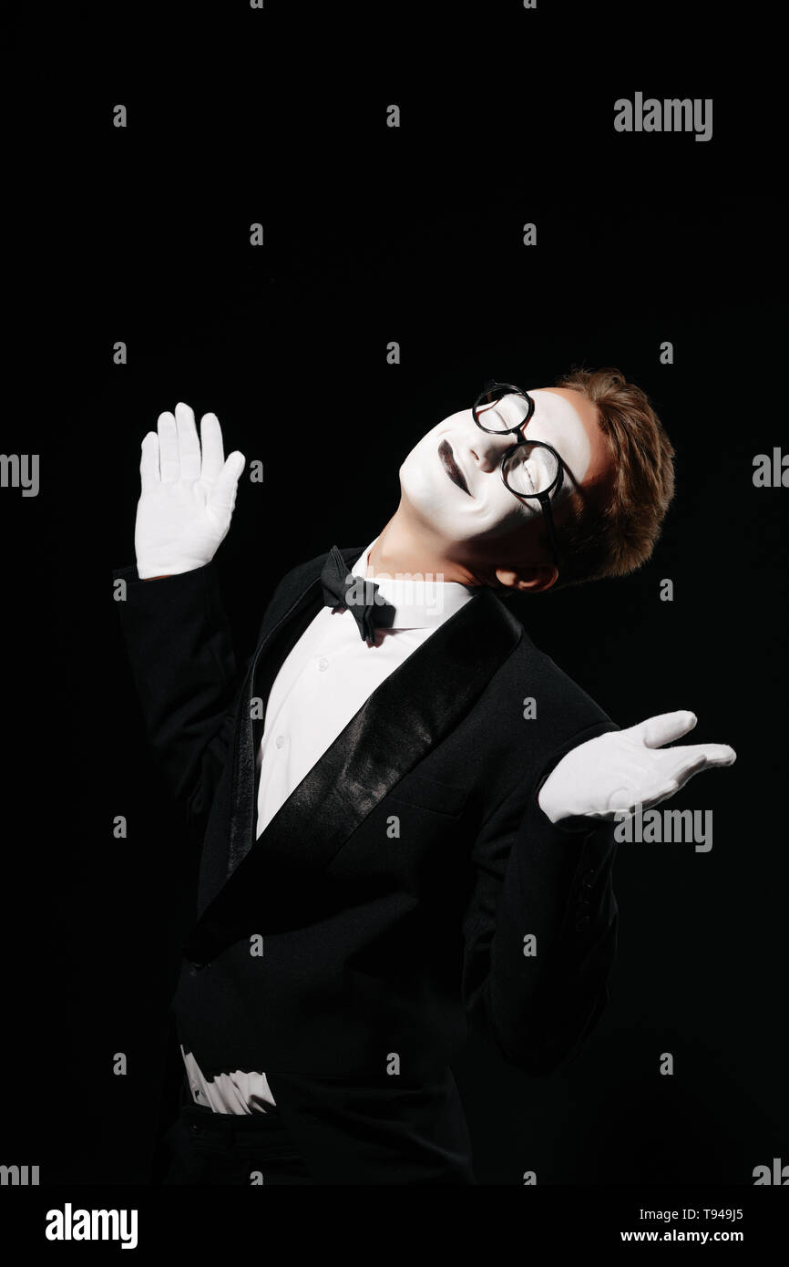 portrait of smiling mime man in tuxedo and glasses on black background - Stock Image
