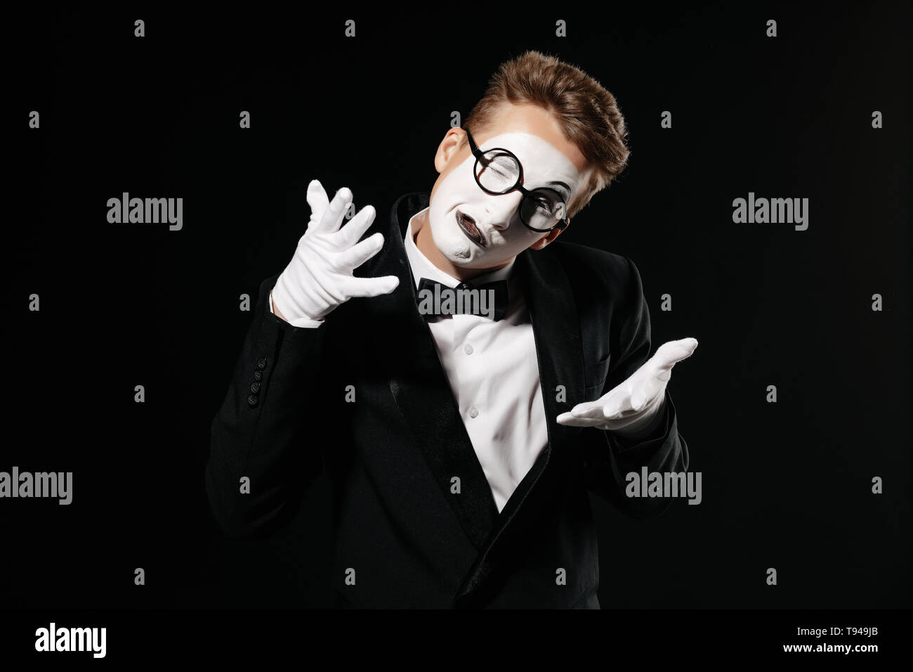 portrait of mime man in tuxedo and glasses on black background - Stock Image