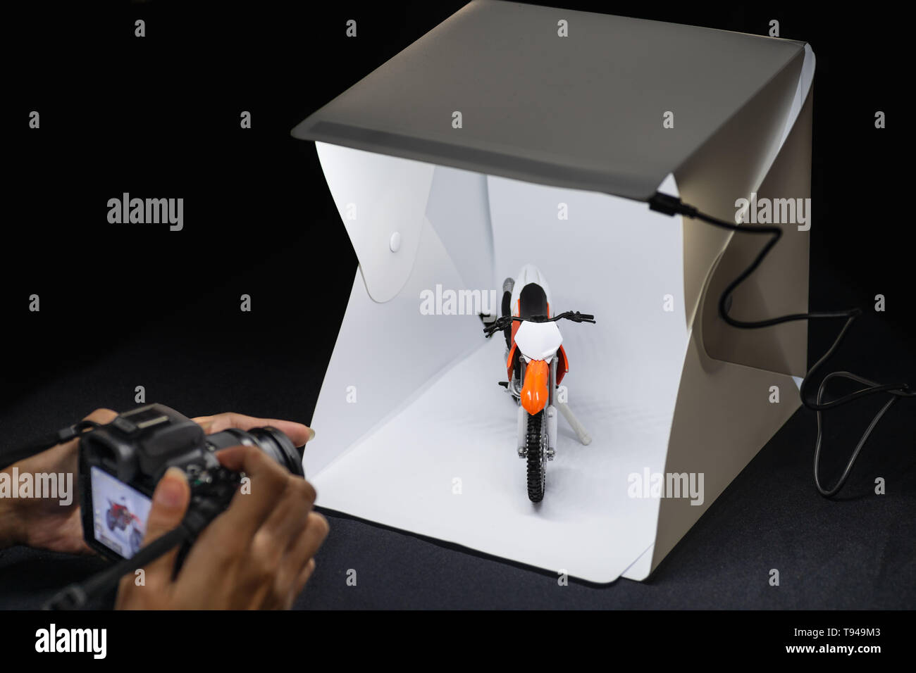 Amateur photographer working on mirrorless camera to shooting motrocycle model in mini lightbox - Stock Image