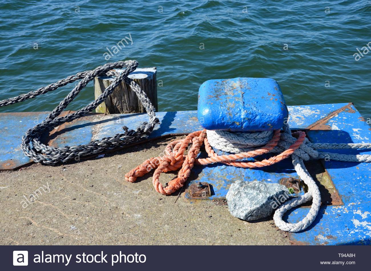 Closeup of ropes anchoring boats at the landing stage, poles, waterfront, sunny, Island Ruegen, Mecklenburg West Pomerania, Germany - Stock Image