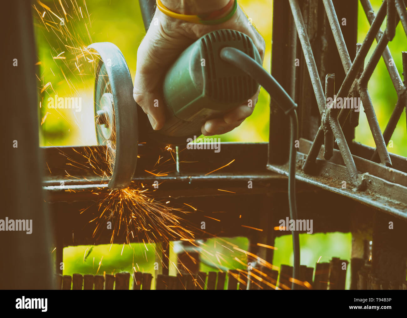 Man using angle grinder, cutting metal, a lot of flashing sparks are flying. - Stock Image