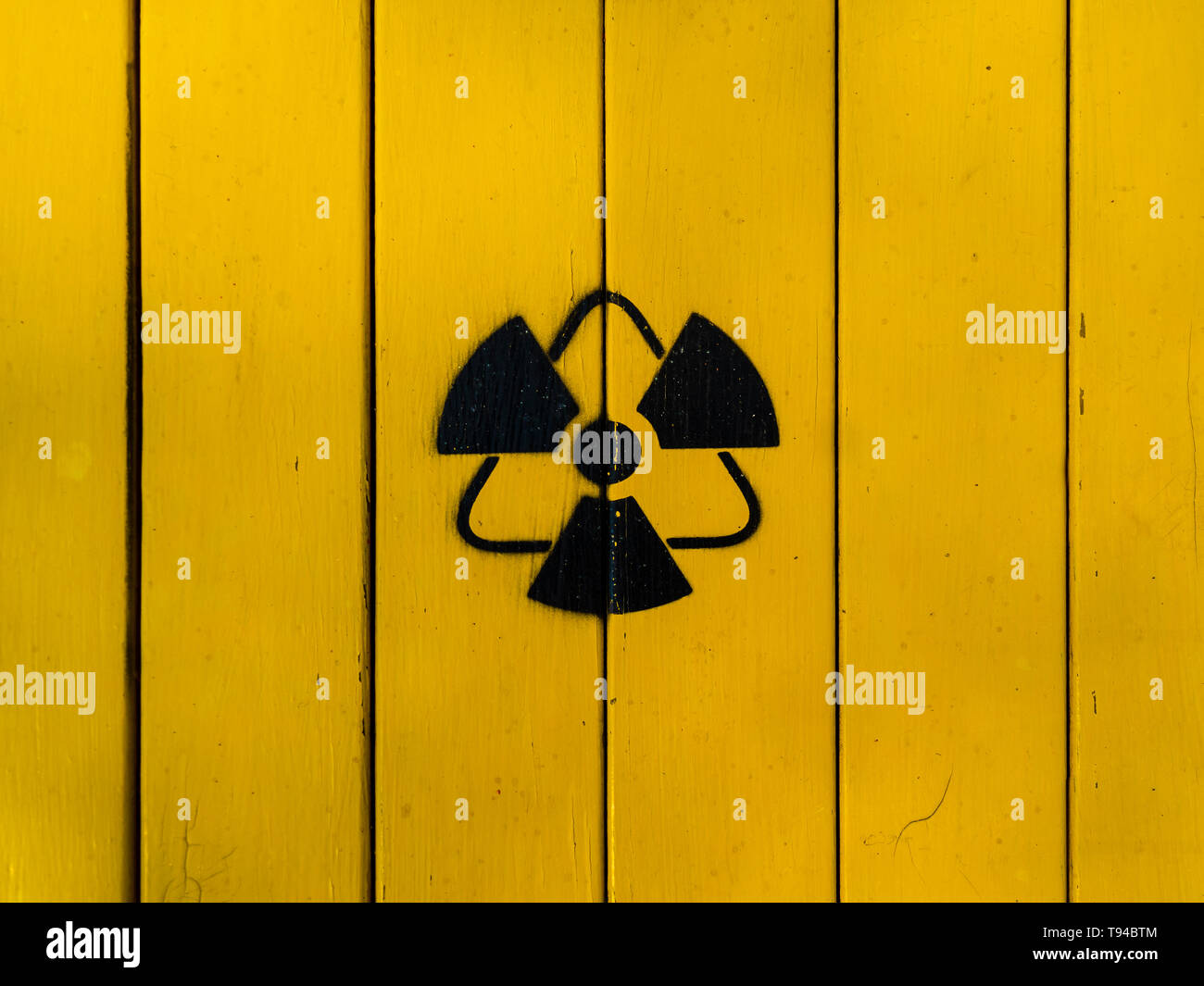 Sign of radiation on a yellow wooden board. Radioactive sign - symbol of radiation. Yellow and black radioactive hazard (ionizing radiation) nuclear d - Stock Image