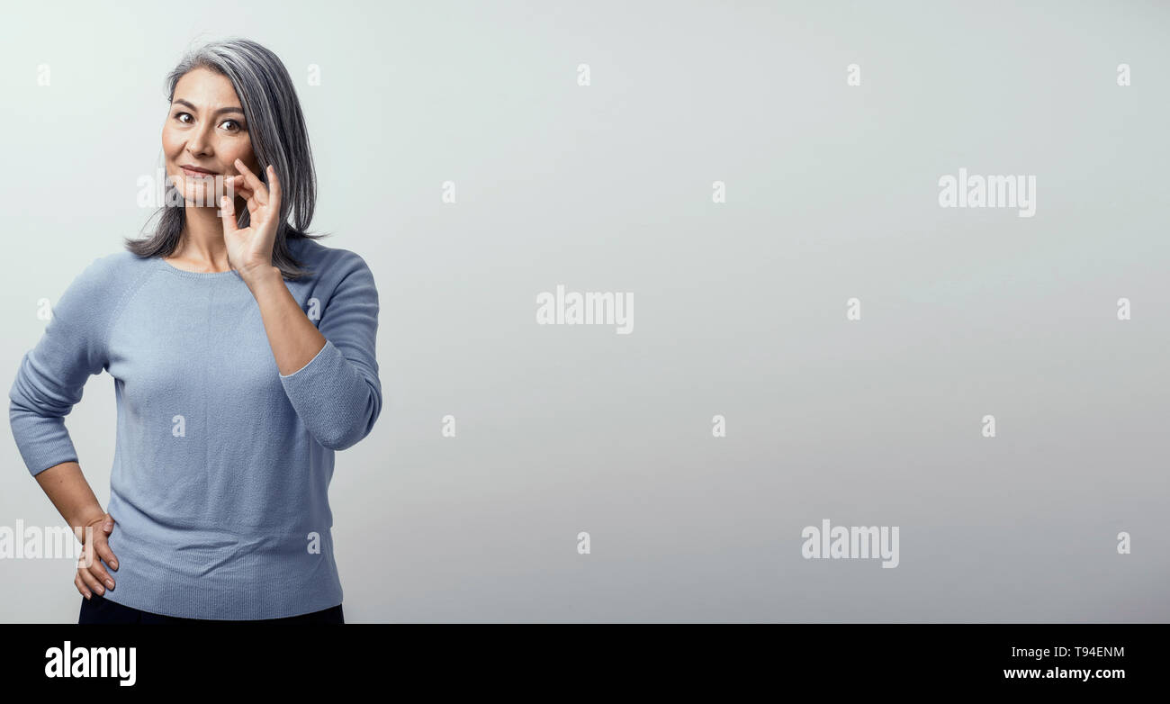 Smiling Asian woman touches her grey hair - Stock Image
