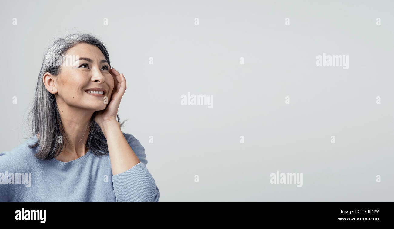 Side profile of charming asian woman smiling on white background - Stock Image