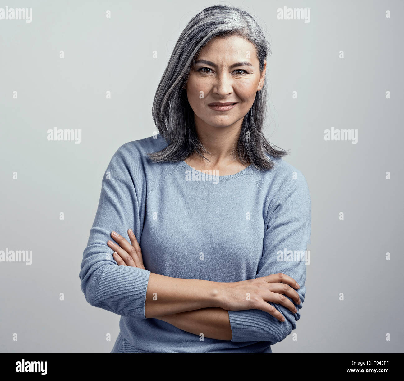 Asian senior woman with crossed arms shows dissproval - Stock Image