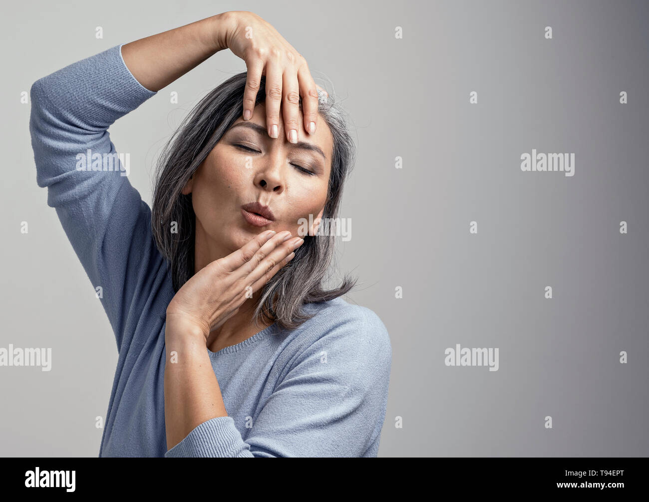 Attractive Asian woman is emotionally posing touching her head with hands - Stock Image