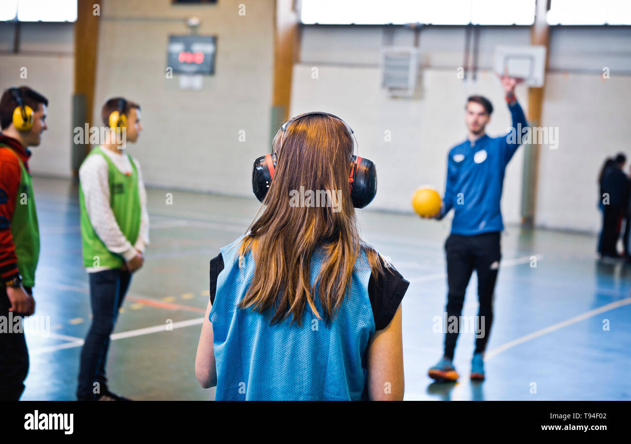 Disability awareness in the school environment. Young secondary-school pupils practicing a sport with earmuffs to figure out how it is to be deaf - Stock Image