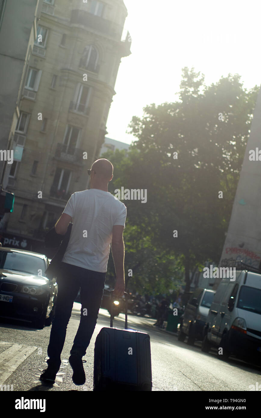 A local business man strolling and walking in the city centre of Paris exploring the city throwing trash in the bin - Stock Image