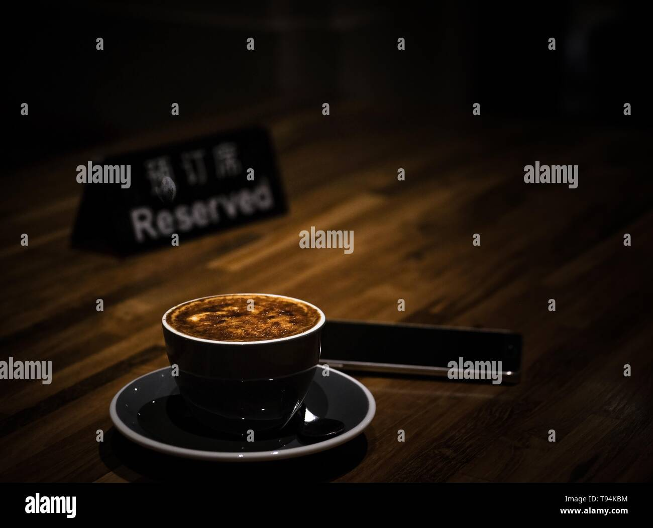 A cup of espresso with a phone and a sign 'Reserved' on a wooden surface  Translation: Reserved - Stock Image