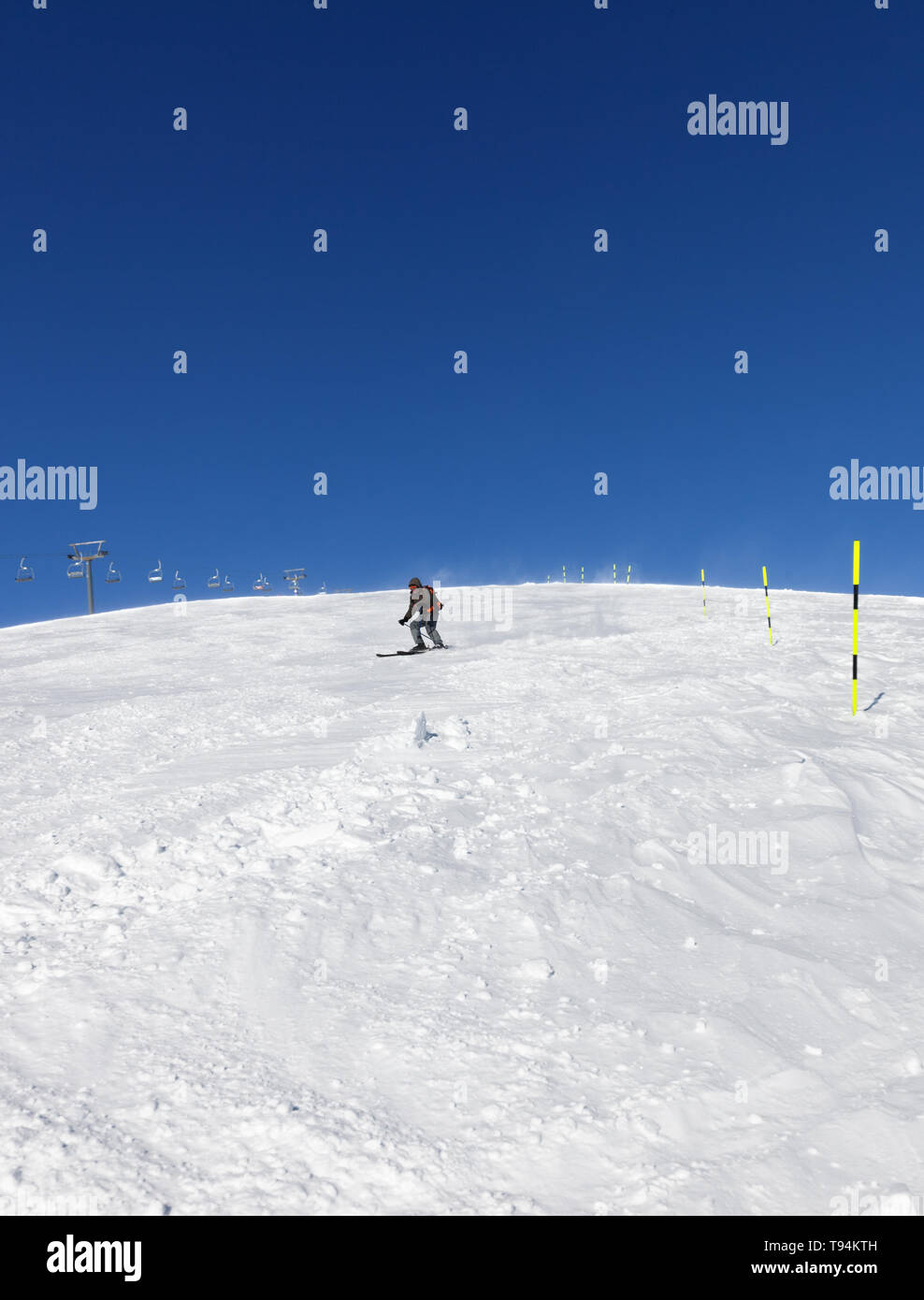 Skier downhill on snowy ski slope in sunny winter day. Caucasus Mountains, Georgia, region Gudauri. Wide angle view. - Stock Image