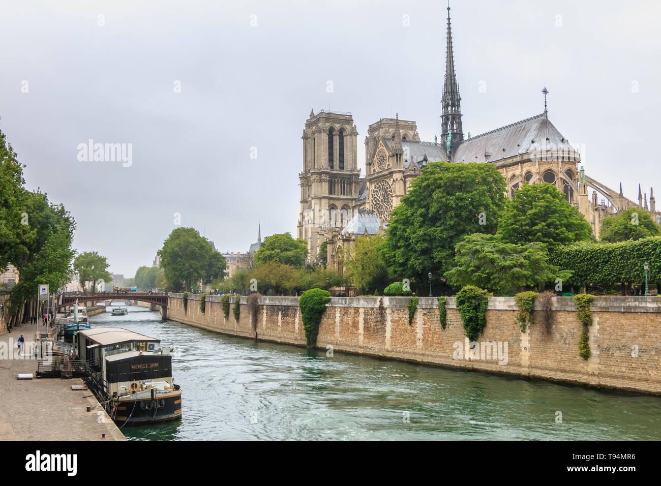 Paris, France - May 8, 2017 - Side view of Notre Dame Cathedral on the Seine with barges on a spring day - Stock Image