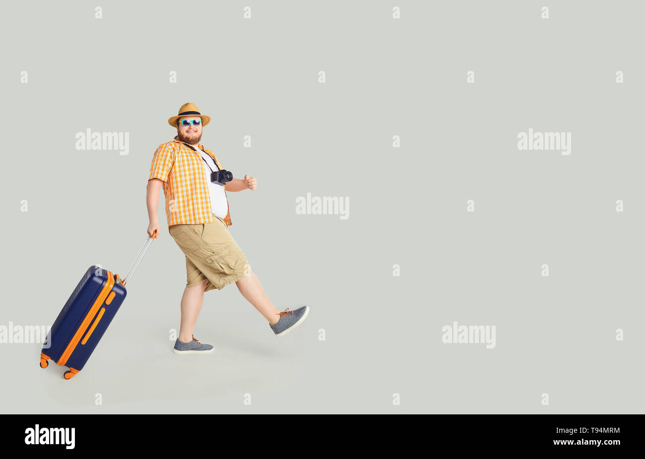 Funny fat man with a suitcase goes to travel in gray background. - Stock Image