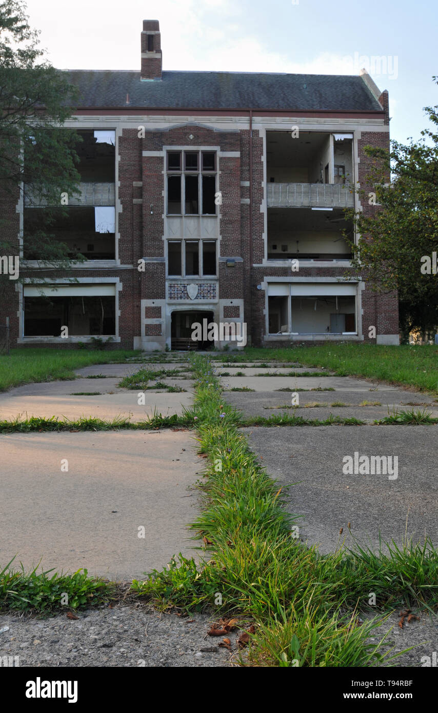 An overgrown walkway leads to an abandoned public school in Detroit, Michigan. All of the building's windows and doors have been broken or removed. - Stock Image